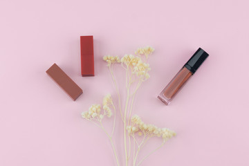 Lipsticks and lip gloss decorate with white dried flowers on pastel pink background