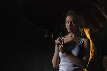 Girl in the white shirt with black umbrella, water drops and dark walls background