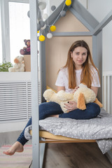Young woman in children room with toy