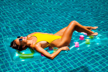 amazing beautiful girl in a yellow bikini air mattress swims in the pool of a luxury hotel, summer vacation, happiness, travel, smile joy