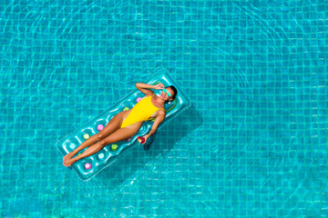 amazing beautiful girl in a yellow bikini air mattress swims in the pool of a luxury hotel, summer vacation, happiness, travel, smile joy, listening to music, drinking cocktail, top view