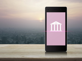 Bank icon on modern smart phone screen on wooden table over city tower at sunset, vintage style, Mobile banking concept
