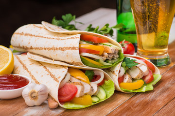 Tortilla wraps with grilled chicken and fresh vegetables and glass of beer
