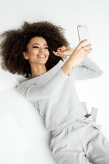 Closeup Portrait Of Beautiful Smiling Black Woman With Smartphone Shooting Selfie And Lying On White Background