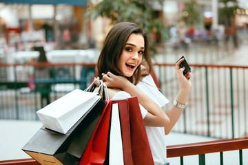 Shopping With Credit Card. Woman With Shopping Bags In Mall.