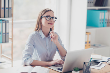 Portrait of thoughtful, charming, stylish, cute, nice woman with hairstyle having pen in hand, dreaming about vacation, weekend, rest, trip, sitting in work place, station at desktop
