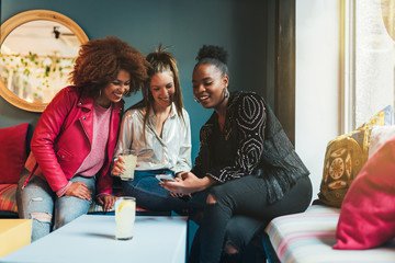 Group of three beautiful young multiracial women sitting in a coffee shop interacting on the mobile phone