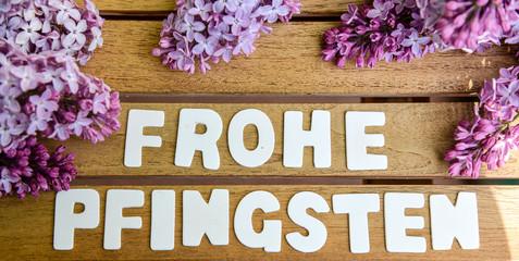 Frohe Pfingsten Wörter auf einem Holtbrett mit Flieder Blumenstrauß