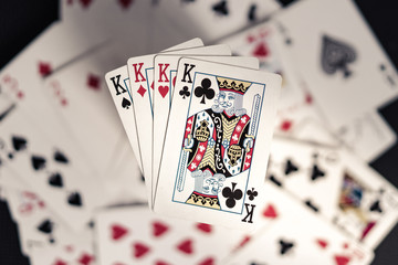 Four kings on top of old playing card