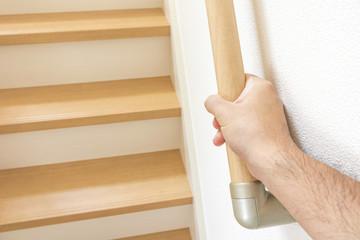 階段の手すりと男の手
