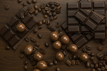 Assorted milk and dark chocolate with coffee beans scattered on a dark brown surface in a full frame close up background from above