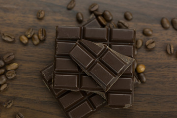 Circular milk chocolate bonbons with coffee beans and a broken slab of dark chocolate in a random scatter on a brown table