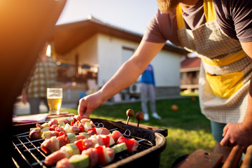 Foto auf Leinwand Bier / Apfelwein Dedicated man turning vegetables and meat on a stick to grill on other side as well while rest of the family is scattered around the house yard.