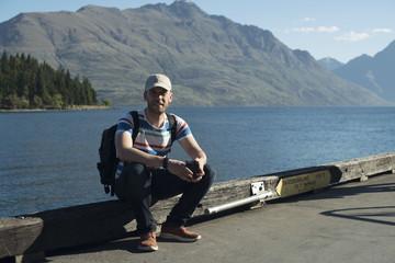 Hombre joven con gorra sentado al atardecer en un puerto