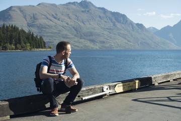 Hombre joven sentado al atardecer en un puerto