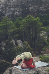 Mid aged bald man doing pilate exercise  in a rocky scenery in the forest, the roll over exercise