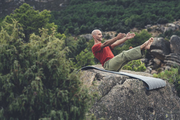 Mid aged bald man doing pilate exercise  in a rocky scenery in the forest, the teaser exercise