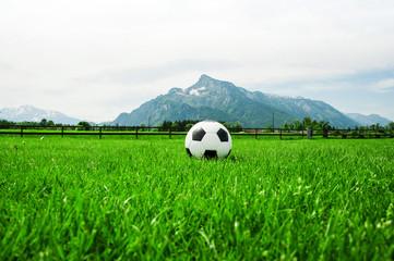 Fussball Ball auf grüner Wiese mit Bergen im Hintergrund im Frühling