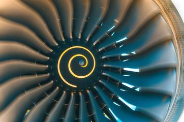 Background turbine blades rotate jet engine aircraft close up.