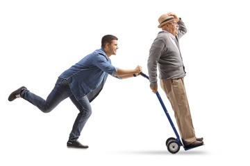 Young man pushing a hand truck with a mature man riding on it