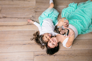 Mother and daughter beautiful and happy doing selfie in turquoise skirts lying on laminate flooring home top view