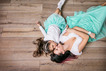 Mother and daughter beautiful and happy in turquoise skirts lie on laminate flooring home top view