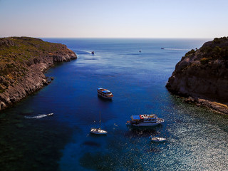 Aerial shot of beautiful blue lagoon at hot summer day with sailing boat. Top view of people are swimming around the boat.