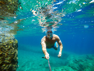 Door stickers UFO Underwater view of a young diver man swimming in the turquoise sea under the surface with snorkeling mask for summer vacation while taking a selfie with a stick.