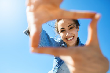 portrait of a young smiling attractive woman in jeans clothes at sunny day on the blue sky background. woman shows a frame from hands like photo. Photo Frame Hands Made By A Hipster young girl