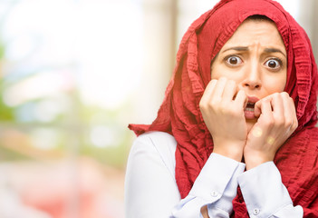 Young arab woman wearing hijab terrified and nervous expressing anxiety and panic gesture, overwhelmed