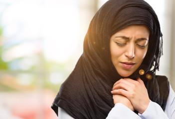 Young arab woman wearing hijab crying depressed full of sadness expressing sad emotion