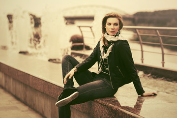 Happy young fashion woman in leather jacket outdoor