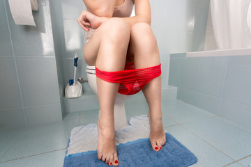 Closeup photo of sexy young woman in red panties sitting on toilet