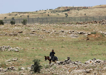 A man sits on a horse near the Israeli-occupied Golan Heights, in Quneitra