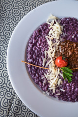 Italian specialty: Purple colored risotto with minced meat and parmesan cheese served on the table with tablecloth