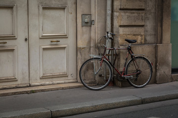 Bicycle parked on the sidewalk against a grunge wall in front of old wooden doors in Paris, France conceptual of urban transport