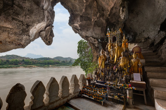 View of the Mekong River and many golden and wooden Buddha statues and religious offerings inside the Tham Ting Cave at the famous Pak Ou Caves near Luang Prabang in Laos.