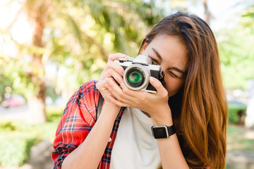 Close up of young Asian woman snap her camera outdoor and enjoyed her city lifestyle on weekend. Young Woman and her city lifestyle along the street. Outdoor activity and city lifestyle concept.