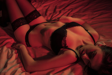 A young girl lies on a bed in sexy lingerie. top view in red light