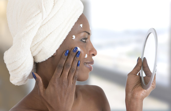 Portrait view of beautiful african american young woman getting ready in home bathroom , applying moisturising cosmetics, cream, mirror face reflection,
