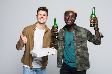 Portrait of a two happy mixed race young men drinking beer and eating pizza while standing isolated over white background