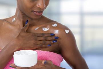 beautiful black skin woman taking care of her body applying moisturizing cream on shoulder