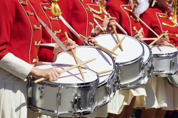 Closeup of group of girls of fans in red military uniform with drums.