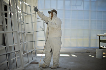 Mid adult man in protective clothing spray painting window frames inside a garage.