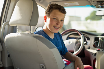 Portrait of a smiling teenage boy sitting in a car.