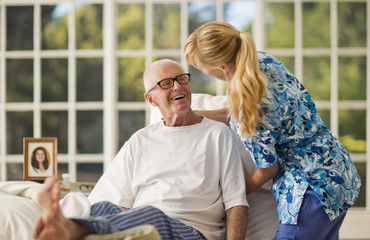 Smiling senior man being comforted by a female nurse inside his bedroom.