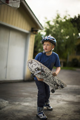 Young boy holding his skateboard while standing on a residential driveway.