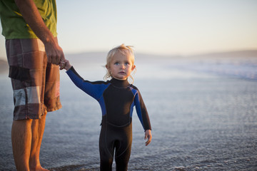 Young toddler holding her father's hand while standing next to a lake wearing a wetsuit.