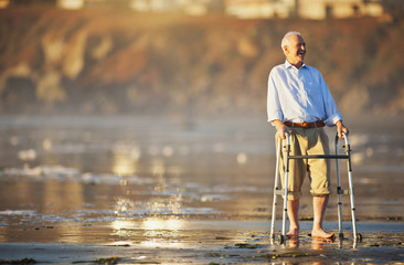 Smiling senior man leaning on a walking aid while at the beach.