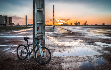 bicycle in the puddles with sunset background